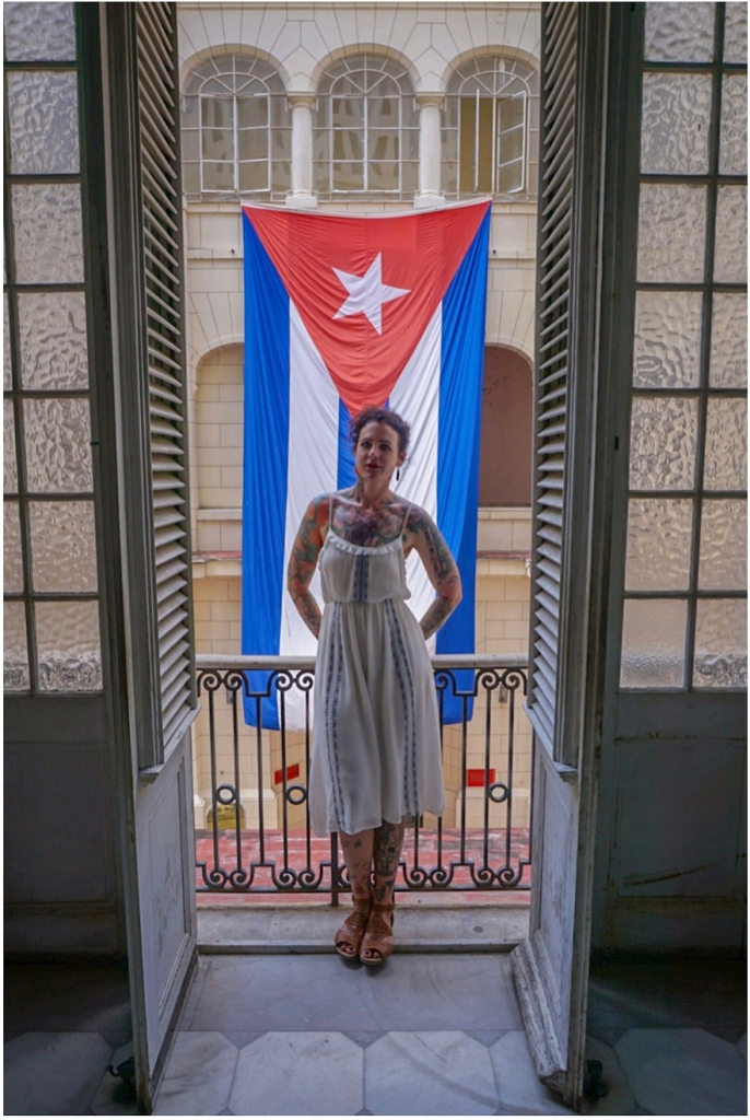 Ellen stands in a doorway to a Juliet balcony on an upper level of the Museo de la Revolución. She's wearing a white summer dress with blue details and tan sandals. Her hair is pinned up, and she has on dangly earrings. Her multiple tattoos are visible and she stands with her arms on the railing behind her; she's not smiling but she looks happy.
